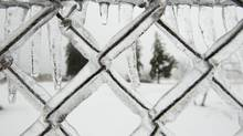 A chain link fence is coated with ice at Mount Hamilton Cemetery in Hamilton on Dec. 22, 2013. (Peter Power/The Globe and Mail)
