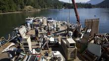 Volunteers aboard the HMCS Annapolis remove metal to be sold for scrap as the ship sits in Long Bay off of Gambier Island near Vancouver July 23, 2011 before being turned into a dive wreck. (John Lehmann/The Globe and Mail)