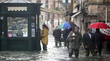 People walk in a flooded street during a period of seasonal high water in Venice November 1, 2012. The water level in the canal city rose to 140 cm above normal, according to the monitoring institute. (Manuel Silvestri/Stringer/Reuters)