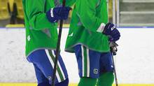 Henrik Sedin #33 of the Vancouver Canucks and teammate Dan Hamhuis (left) share a laugh as they participate in an informal skate at UBC in Vancouver September 17, 2012. (Jeff Vinnick For The Globe and Mail)