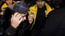 Canadian musician Justin Bieber is swarmed by media and police officers as he turns himself into city police in Toronto on Wednesday, January 29, 2014. (Nathan Denette/THE CANADIAN PRESS)