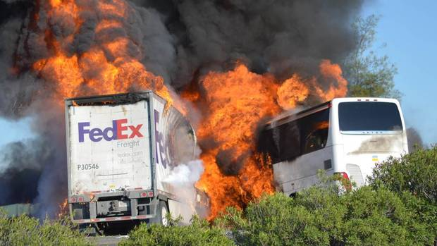 Massive flames are seen devouring both vehicles just after a crash in California on April 10, 2014. The FedEx tractor-trailer crossed a grassy freeway median in Northern California and slammed into the bus carrying high school students on a visit to a college. (JEREMY LOCKETT/ASSOCIATED PRESS)