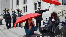 Dominatrix Terri-Jean Bedford (right) sits on the front steps to the Supreme Court of Canada in Ottawa on Thursday, June 13, 2013. The court is hearing arguments on the constitutionality of Canada's prostitution laws. (Sean Kilpatrick/THE CANADIAN PRESS)