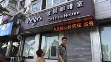 A boy looks up as he walks past the closed coffee shop owned by Canadian couple Kevin Garratt and Julia Dawn Garratt in Dandong, Liaoning province, August 5, 2014. REUTERS/Ben Blanchard (CHINA - Tags: POLITICS CRIME LAW BUSINESS TPX IMAGES OF THE DAY) (STAFF/REUTERS)