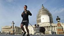 A man jogs with his dog past the U.S. Capitol in Washington (KEVIN LAMARQUE/REUTERS)