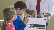 Ella-Grace and Xavier watch their father, Liberal Leader Justin Trudeau, place his vote in the ballot box in Montreal on Oct. 19, 2015. (POOL/REUTERS)