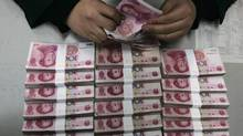 An employee counts yuan banknotes at a branch of Bank of China in Taiyuan, Shanxi province. (STRINGER SHANGHAI/REUTERS)