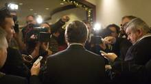 "Federal Finance Minister Jim Flaherty, back to the camera, said he won't move ahead with the proposed national regulator law, but that the government ""will review the decision carefully and act in accordance with it."" (GEOFF HOWE/THE CANADIAN PRESS)"