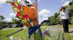 A woman walks through a field where 14-year-old Adrian Johnston was shot and killed. A memorial with bandanas, flowers and a teddy bear sit at the side of the road.