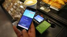 A customer uses an Apple Inc. iPhone to pay via the Apple Pay system, from their Nationwide account, at the check-out till in London, U.K., July 14, 2015. (Chris Ratcliffe/Bloomberg)