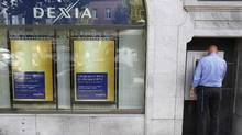 A man withdraws money from a Dexia ATM in central Brussels September 27, 2011. (FRANCOIS LENOIR/REUTERS)