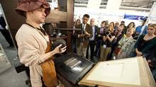 A stand attendant in traditional garb demonstrates the use of a Gutenberg printing press at the 63rd Frankfurt Book Fair October 14, 2011. (JOHN MACDOUGALL/AFP/Getty Images)