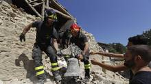 Firefighters retrieve a bell from a church in the small town of Rio, near Amatrice, central Italy, Sunday, Aug. 28, 2016. Bulldozers with huge claws pulled down dangerously overhanging ledges Sunday in Italy's quake-devastated town of Amatrice as investigators worked to figure out if negligence or fraud in building codes had added to the quake's high death toll. (AP Photo/Andrew Medichini) (Andrew Medichini/AP)