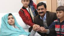 Malala Yousafzai is seen with her father Ziauddin and her two younger brothers Khushal Khan and Atal Khan (R), as she recuperates at the The Queen Elizabeth Hospital in Birmingham, in this photograph taken October 25, 2012 and released October 26, 2012 (Handout/Reuters)
