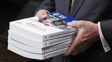 Canada's Finance Minister Jim Flaherty holds copies of his budget in the House of Commons in Ottawa on March 22, 2011. (CHRIS WATTIE/Chris Wattie/Reuters)