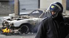 A police officer in riot gear stands in front of a burning car on a street in Hackney, east London. (TOBY MELVILLE/REUTERS)