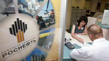 A employee of state-owned Sberbank explains to a man how to fill a subscription form for Rosneft shares in one of the bank's central Moscow offices June 26, 2006. (ALEXANDER NATRUSKIN/REUTERS)