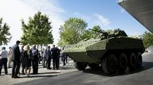 Dignitaries gather around a Light Armoured Vehicle (LAV) III prior to an announcement in Toronto June 16, 2015. (Darren Calabrese For The Globe and Mail)