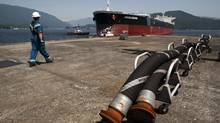 A Kinder-Morgan employee make his way towards the Aqualegend crude oil tanker as it approaches the Kinder Morgan Westridge marine terminal in Burnaby, British Columbia, Sunday, July 8, 2012. (Rafal Gerszak For The Globe and Mail)