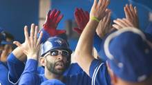 Toronto Blue Jays' Jose Bautista is congratulated in the dugout after he hit a two run home run in the first inning of their AL baseball game against the New York Yankees in Toronto (FRED THORNHILL/THE CANADIAN PRESS)