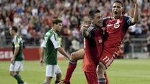 Luis Silva, right, celebrates with Toronto FC teammate Eric Hassli after scoring his team's second goal against the Portland Timbers at BMO Field on Wednesday. (Chris Young/THE CANADIAN PRESS)