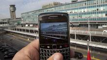 A BlackBerry user takes a picture of Pierre Elliott Trudeau Airport, Wednesday, October 12, 2011 in Montreal. (Ryan Remiorz/THE CANADIAN PRESS)