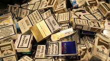 """In this Jan. 4, 2007 file photo, discarded cigarette cartons lie on the floor as people gather at a one hour """" Stop Smoking"""" promotion in a bar in central London. (ALASTAIR GRANT/AP)"""