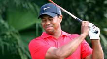 Tiger Woods grimaces after hitting from the 12th tee during the final round of the Cadillac Championship golf tournament Sunday, March 11, 2012, in Doral, Fla. Woods withdrew from the tournament, and was driven away in a cart. (Wilfredo Lee/AP)