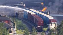 A tanker continues to burn as fire fighters douse rail containers in downtown Lac-Mégantic, Que., on July 7, 2013. (MOE DOIRON/THE GLOBE AND MAIL)