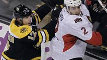 Boston Bruins left wing Brian Rolston (12) checks Ottawa Senators defenseman Jared Cowen (2) into the boards during the first period of an NHL game in Boston Tuesday, Feb. 28, 2012. (Elise Amendola/AP)