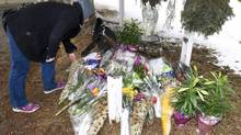 Mourners drops off flowers at a makeshift memorial near the scene of the a multiple fatal stabbing incident in Calgary on April 16, 2014. (Larry MacDougal/THE CANADIAN PRESS)