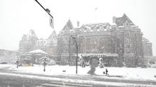 A pedestrian braves the heavy snowfall in front of the Fairmont Empress Hotel in Victoria, Feb. 23, 2011. (Deddeda Stemler for the Globe and Mail)