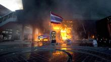 "A statue of Buddha and a torn Thai national flag remain in front of Bangkok's Central World shopping mall, which was gutted by fire after army soldiers penetrated an encampment of anti-government ""red shirt"" protesters May 19, 2010. (ADREES LATIF/REUTERS)"