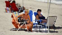 French-Canadian snowbirds Pierrette Bolduc and Gisele Barbeau relax on Hollywood Beach in Florida last year