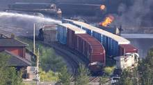 A tanker continues to burn as firefighters douse rail containers in downtown Lac-Mégantic, Que., on Sunday. (MOE DOIRON/THE GLOBE AND MAIL)