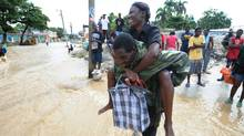 A man helps a woman to cross a flooded road for money in Leogane, 33 km south of Port-au-Prince, on November 6, 2010. (THONY BELIZAIRE/THONY BELIZAIRE/AFP/Getty Images)