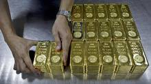 A technician prepares 1 Kg gold bars of 995.0 purity to pack for delivery at the Emirates Gold company in Dubai, United Arab Emirates, on Tuesday, Oct. 9, 2012. (Kamran Jebreili/The Associated Press)