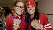 Canadian divers Roseline Filion, left, and Meaghan Benfeito display their bronze medals at Trudeau Airport in Montreal, Monday, August 13, 2012, as they return home from the London 2012 Olympics. (The Canadian Press)