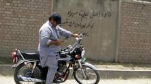 A man sits on a motorbike in front of a wall with a graffiti message at Mission Hospital in Bannu, in Khyber-Pakhtunkhwa province July 11, 2014. The Afghan Taliban have urged Muslims to avoid extremism and remain united, a message apparently aimed at the Islamic State (ISIL), which recently declared an Islamic caliphate in territory it controls in Iraq and Syria. (STRINGER/PAKISTAN/REUTERS)