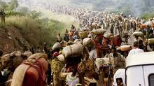 Rwandese refugees cross Rusumo border to Tanzania from Rwanda in this May 30, 1994 file photo. (JEREMIAH KAMAU/REUTERS)