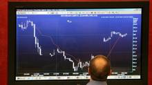 A trader studies a graph on a screen at the Moscow Interbank Currency Exchange (MICEX) in Moscow May 23, 2006. (ALEXANDER NATRUSKIN/REUTERS)