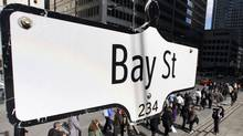 The Bay Street sign is shown in the heart of the financial district as people walk by in Toronto. (MARK BLINCH/MARK BLINCH/REUTERS)