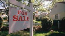 For sale sign hanging in front of house (Stockbyte/Getty Images)