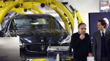 Fiat chairman John Elkann, right, and Fiat's chief executive Sergio Marchionne stand near a new car during the opening of a new Maserati plant in Turin Jan. 30, 2013. (STEFANO RELLANDINI/REUTERS)