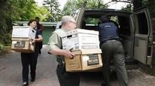 Agents of the Royal Gendarmerie of Canada carry boxes of documents from the home of Jacques Corriveau, Wednesday July 4, 2007, in Saint-Bruno-de-Montarvile, Que (Francois Roy/CP)