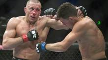 In this March 16, 2013 file photo, Georges St-Pierre, left, lands a blow to Nick Diaz, from the United States, during their UFC 158 welterweight mixed martial arts title fight in Montreal. The UFC is celebrating its 20th anniversary this weekend by putting its most decorated champion into what's likely his toughest matchup in years. Welterweight kingpin St-Pierre realizes he could struggle against streaking contender Johny Hendricks at UFC 167 in Las Vegas. (Graham Hughes/THE CANADIAN PRESS)