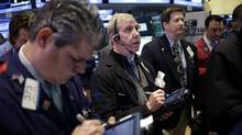 Traders work on the floor at the New York Stock Exchange on April 22, 2013. North American stocks were relatively unchanged in midday trading. (Seth Wenig/AP)