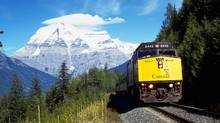 A Via Rail passenger train passes by Mount Robson, highest peak in the Canadian Rockies. (Canadian Press)