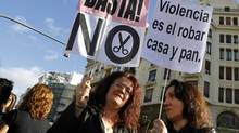 Civil servants hold placards as they protest against austerity measures in central Valencia, Oct. 26, 2012. (HEINO KALIS/REUTERS)