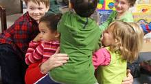 Liberal Leader Michael Ignatieff is smothered as he gets a group hug from children after reading to them at an Ottawa daycare on Tuesday, October 20, 2009. (FRED CHARTRAND)